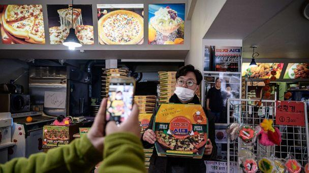 PHOTO: A customer poses before a photo of film director Bong Joon-ho at the 'Sky Pizza' restaurant in Seoul on February 13, 2020. (Ed Jones/AFP via Getty Images)