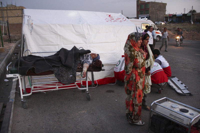 A woman lies injured on a stretcher in a street after an earthquake in the city of Varzaqan in northwestern Iran, on Saturday, Aug. 11, 2012. A 6.2-magnitude earthquake hit the towns of Ahar, Haris and Varzaqan in East Azerbaijan province in northwestern Iran on Saturday, state TV said. Iran is located on seismic fault lines and is prone to earthquakes. It experiences at least one earthquake every day on average, although the vast majority are so small they go unnoticed. (AP Photo/Mehr News Agency, Hamed Nazari)
