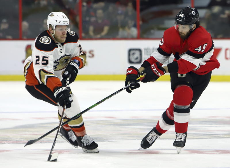 Anaheim Ducks right wing Ondrej Kase (25) controls the puck as Ottawa Senators right wing Scott Sabourin (49) defends during the first period of an NHL hockey game, Tuesday, Feb. 4, 2020 in Ottawa, Ontario. (Fred Chartrand/The Canadian Press via AP)
