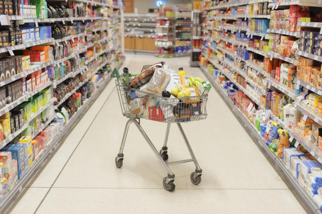 Full shopping cart in supermarket aisle. Photo: Getty