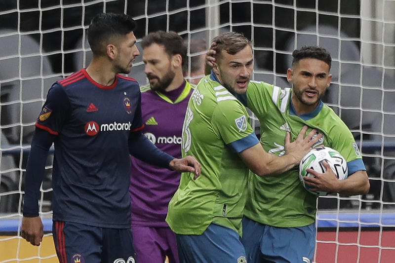 Seattle Sounders midfielder Cristian Roldan, right, greets forward Jordan Morris, second from right, after Morris assisted him on a goal that was called back due to Morris being off-sides during the second half of an MLS soccer match against the Chicago Fire, Sunday, March 1, 2020, in Seattle. (AP Photo/Ted S. Warren)