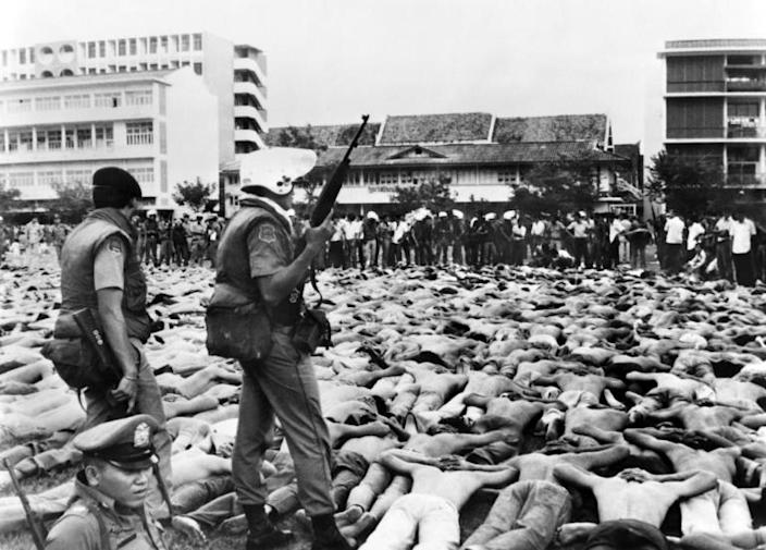 Shirtless students lie facedown on the ground, as police stand guard on the Thammasat University campus in Bangkok on October 6, 1976