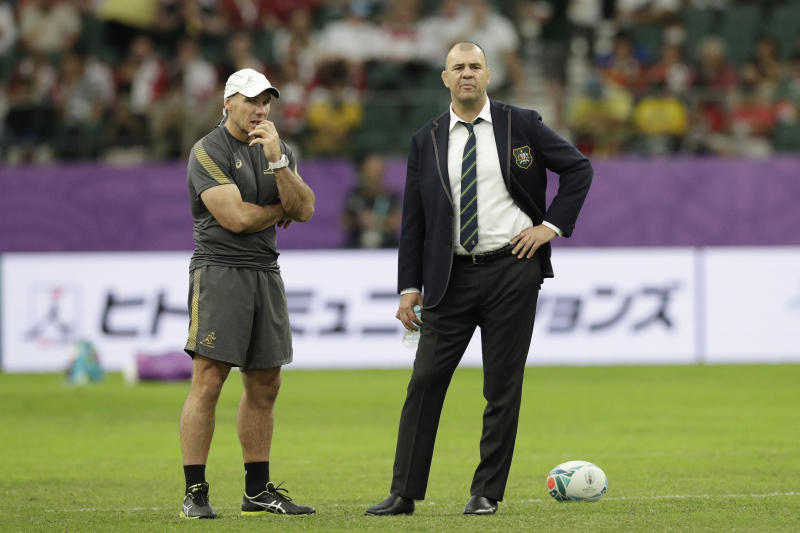 Australia coach Michael Cheika, right, watches as his team warm up before the Rugby World Cup quarterfinal match at Oita Stadium between England and Australia in Oita, Japan, Saturday, Oct. 19, 2019. (AP Photo/Aaron Favila)
