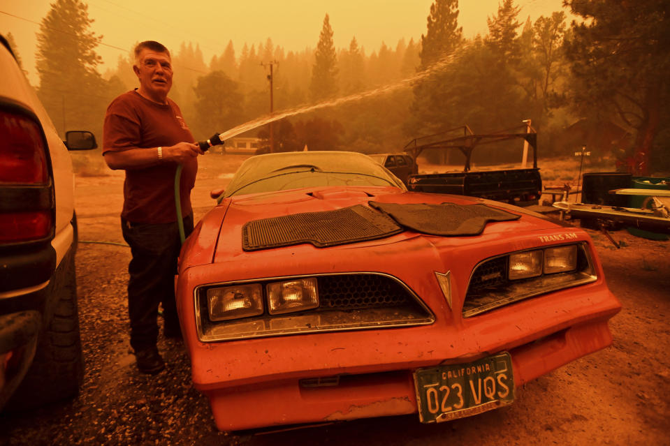 William Deal wets down his 1977 Trans Am as the Dixie Fire approaches Crescent Mills in Plumas County, Calif., Saturday, July 24, 2021. Deal, who lives in a community under evacuation orders, planned to stay to defend his home from the fire. (AP Photo/Noah Berger)
