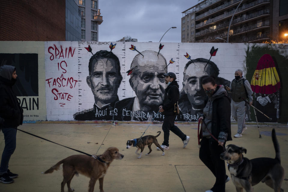 People walk past a graffiti depicting Spain's King Felipe VI, former King Juan Carlos and Spain's late dictator Francisco Franco by artist BlackBlock, in support of Catalan rap artist Pablo Hasel in Barcelona, Spain, Sunday, Feb. 21, 2021. The imprisonment of Pablo Hasel for inciting terrorism and refusing to pay a fine after having insulted the country's monarch has triggered a social debate and street protests. (AP Photo/Felipe Dana)