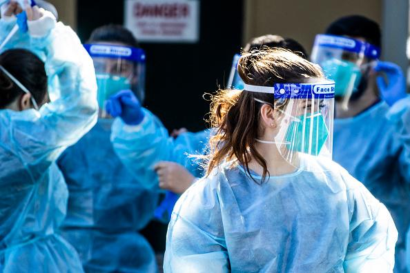 Health care workers are seen at a  pop-up COVID-19 testing clinic in Rushcutters Bay in Sydney, Australia.