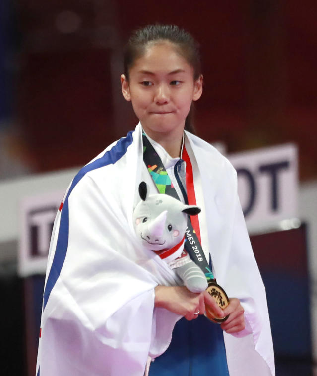 Taiwan's Tzuyun Wen celebrates with medals during the victory ceremony for their women's -55kg kumite karate at the 18th Asian Games in Jakarta, Indonesia, Sunday, Aug. 26, 2018. (AP Photo/Tatan Syuflana)