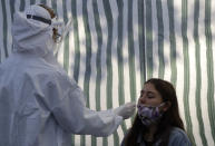 A woman gets tested for COVID-19 at a sampling station in Prague, Czech Republic, Monday, Sept. 21, 2020. The country coped well with the first wave of the coronavirus infections in the spring but has been facing a record surge of the new confirmed cases last week. (AP Photo/Petr David Josek)