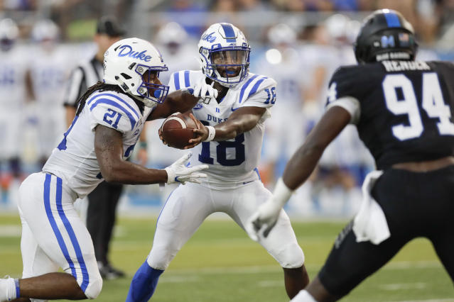 Duke quarterback Quentin Harris (18) hands off to running back Mataeo Durant (21) as Middle Tennessee defensive end Tyshun Render rushes in the first half of an NCAA college football game Saturday, Sept. 14, 2019, in Murfreesboro, Tenn. (AP Photo/Mark Humphrey)