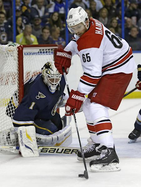 Carolina Hurricanes' Ron Hainsey (65) tries to control the puck as St. Louis Blues goalie Brian Elliott, left, defends during the first period of an NHL hockey game Saturday, Nov. 16, 2013, in St. Louis. (AP Photo/Jeff Roberson)