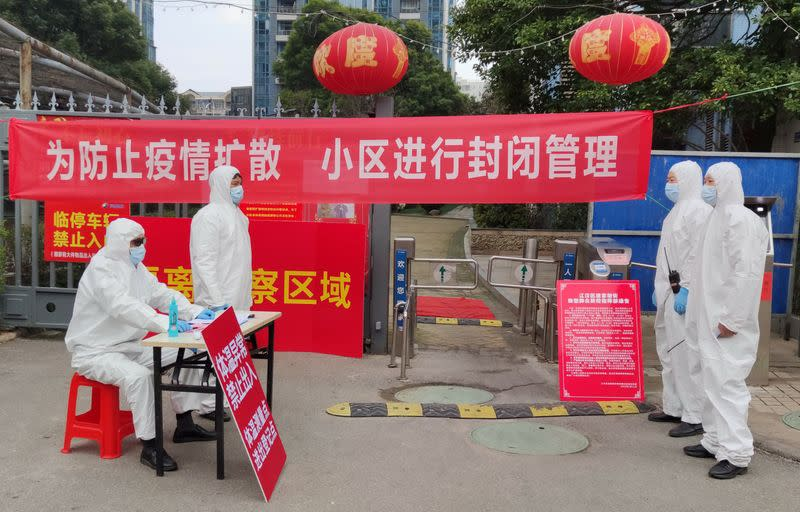 FILE PHOTO: Workers in protective suits are seen at a checkpoint for registration and body temperature measurement, at an entrance to a residential compound in Wuhan