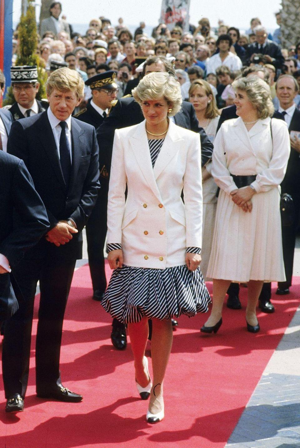 <p>Diana wore an oversized white blazer paired with a striped dress by Catherine Walker while walking the red carpet at the Cannes Film Festival on May 15, 1987.</p>