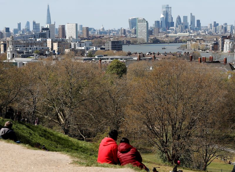 FILE PHOTO: Visitors to Greenwich Park sit and look towards the City of London as lockdown restrictions are eased amidst the spread of the coronavirus disease (COVID-19) pandemic in London