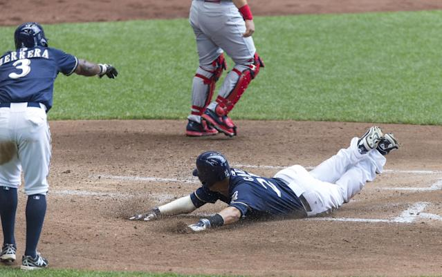 Milwaukee Brewers' Carlos Gomez slides safely home as teammate Elian Herrera gives him the down sign against the St. Louis Cardinals' during the fourth inning of a baseball game Sunday, July 13, 2014, in Milwaukee. (AP Photo/Tom Lynn)