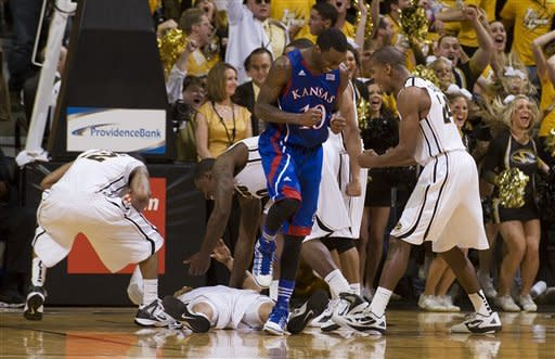 Kansas' Tyshawn Taylor, center, reacts after being called for an offensive foul on Missouri's Michael Dixon, bottom, in the final seconds of the second half of an NCAA college basketball game while Missouri's Kim English, right, Marcus Denmon, left, and Ricardo Ratliffe celebrate on Saturday, Feb. 4, 2012, in Columbia, Mo. Missouri won the game 74-71. (AP Photo/L.G. Patterson)