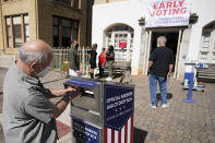 FILE - In this Oct. 19, 2020, file photo, a voter submits a ballot in an official drop box during early voting in Athens, Ga. The county officials who run elections are facing a slate of new punishments as part of a nationwide Republican campaign to roll back access to the ballot, months after many hailed them as heroes for the creative ways they expanded voting access last year during the coronavirus outbreak. (AP Photo/John Bazemore, File)