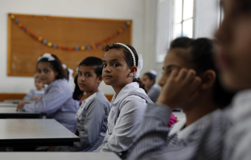 Students sit in their class on the first day of the new school year at the United-Nation run Elementary School at the Shati refugee camp in Gaza City, Saturday, Aug. 8, 2020. Schools run by both Palestinian government and the U.N. Refugee and Works Agency (UNRWA) have opened almost normally in the Gaza Strip after five months in which no cases of community transmission of the coronavirus had been recorded. (AP Photo/Adel Hana)