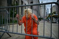 A Donald Trump impersonator poses for photos outside the Criminal Courts building and District Attorneys office in Manhattan