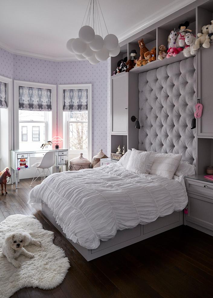 "<div class=""caption""> Bisou has a knack for finding the most comfortable spots in the house, such as this shearling rug in the girl's bedroom. The oversized pale purple tufted headboard was custom-made; its color matches the wallpaper from <a href=""https://www.walnutwallpaper.com"" rel=""nofollow noopener"" target=""_blank"" data-ylk=""slk:Walnut"" class=""link rapid-noclick-resp"">Walnut</a> featuring hundreds of little eyes with eyelashes. </div>"
