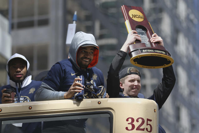 Matt Kennedy holds up the national championship trophy during Villanova's NCAA men's college basketball tournament victory parade, Thursday, April 5, 2018, in Philadelphia. (Tim Tai/The Philadelphia Inquirer via AP)