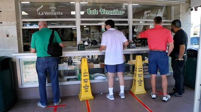 On Saturday, April 17, 2021, people line up for Cuban coffee at the Versailles restaurant in Little Havana, Miami.