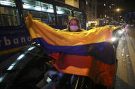 A supporter of former President Alvaro Uribe holds a national flag as she protests the Supreme Court decision to place Uribe under house arrest while it advances a witness tampering investigation against him, in Bogota, Colombia, Tuesday, Aug. 4, 2020. (AP Photo/Fernando Vergara)