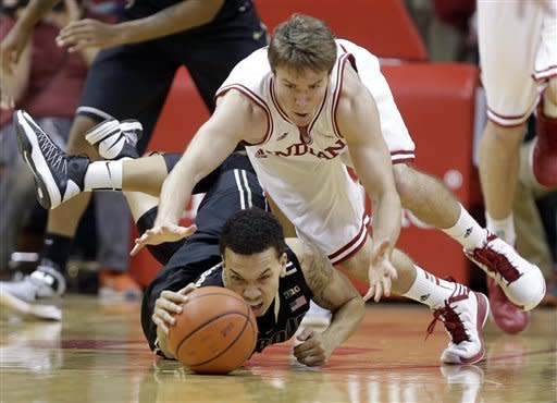 Purdue guard Anthony Johnson, bottom, and Indiana guard Jordan Hulls dive for a loose ball in the second half of a NCAA college basketball game in Bloomington, Ind., Saturday, Feb. 16, 2013. Indiana defeated Purdue 83-55. (AP Photo/Michael Conroy)