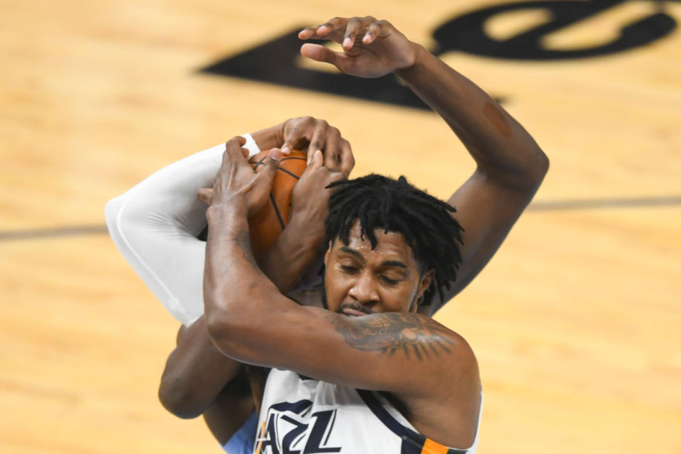 Utah Jazz center Derrick Favors ties the ball up with Memphis Grizzlies forward Jaren Jackson Jr. during the first half of Game 3 of an NBA basketball first-round playoff series Saturday, May 29, 2021, in Memphis, Tenn. (AP Photo/John Amis)