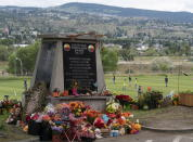 Children play soccer in the background as a memorial is pictured outside the Residential School in Kamloops, British Columbia., Sunday, June, 13, 2021. The remains of 215 children were discovered buried near the former Kamloops Indian Residential School earlier this month. (Jonathan Hayward/The Canadian Press via AP)