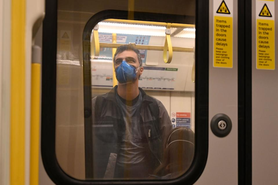 A man wearing a mask stands in an underground train in London on March 14, 2020. - British Prime Minister Boris Johnson, who has faced criticism for his country's light touch approach to tackling the coronavirus outbreak, is preparing to review its approach and ban mass gatherings, according to government sources Saturday. (Photo by Glyn KIRK / AFP) (Photo by GLYN KIRK/AFP via Getty Images)