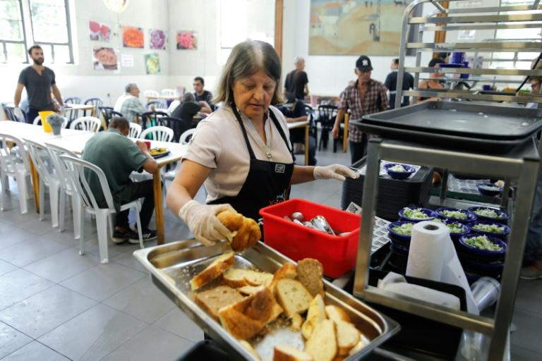 Hundreds of meals are served at the Lasova soup kitchen daily to senior citizens, African migrants, the unemployed and the homeless (AFP Photo/MENAHEM KAHANA)