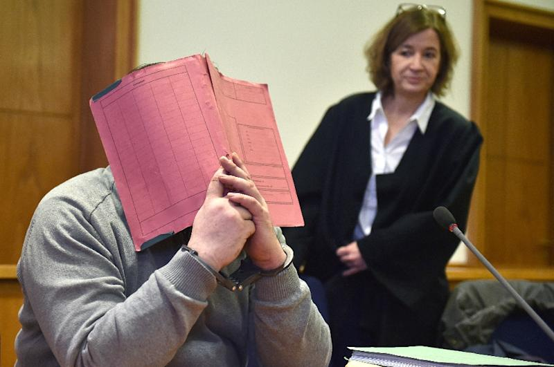 German former male nurse Niels Hoegal hid his face behind a folder in 2015 during his trial at a court in Oldenburg