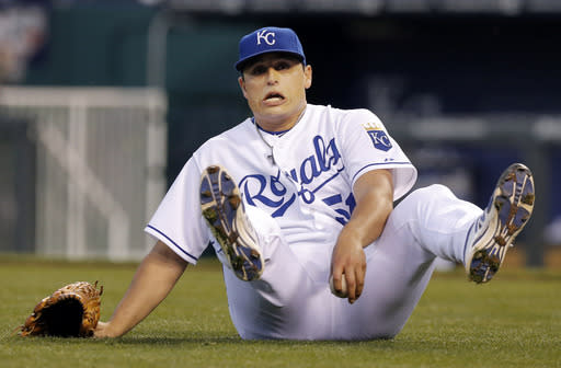 Kansas City Royals starting pitcher Jason Vargas falls while fielding a ground ball hit by Minnesota Twins' Brian Dozier during the third inning of a baseball game at Kauffman Stadium in Kansas City, Mo., Friday, April 18, 2014. Dozier was safe at first base on the play. (AP Photo/Orlin Wagner)