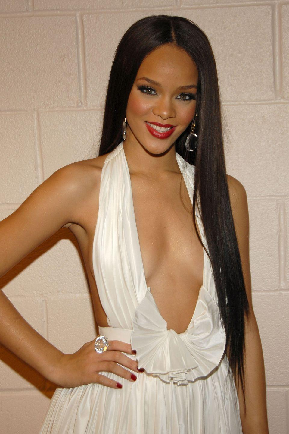 <p>Pin-straight and sleek, Rihanna wears her jet black hair ultra-long. </p>
