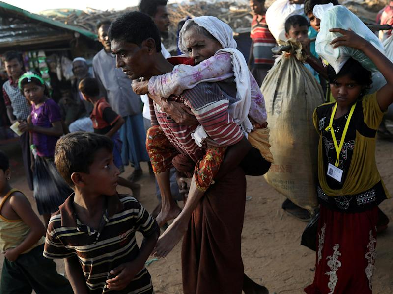 Rohingya refugee Suray Khatun, 70, is carried by her son Said-A-Lam, 38, as they enter Kutupalong refugee camp, near Cox's Bazar, Bangladesh a day after crossing the Myanmar border: REUTERS/Susana Vera