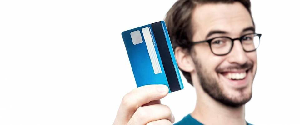 Happy man showing his new credit card