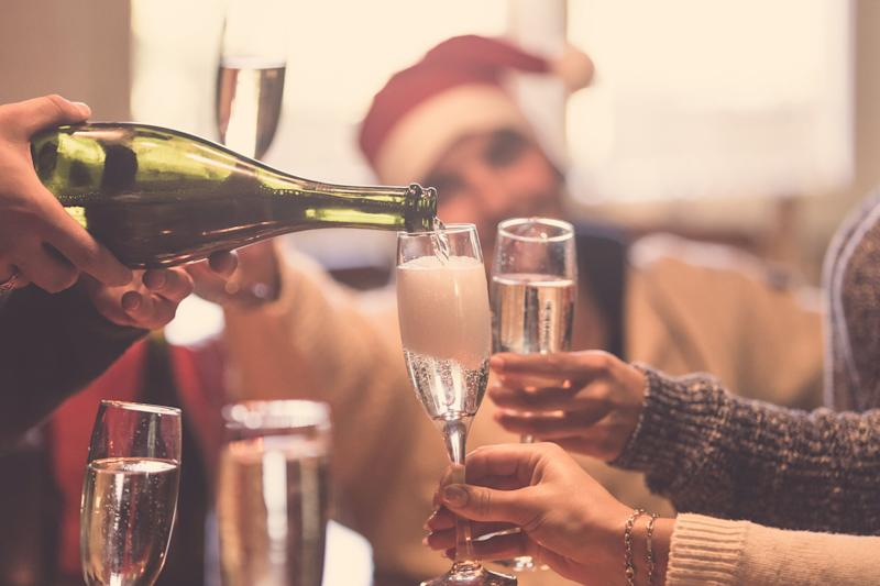 Cropped image of people toasting with champagne celebrating Christmas (Photo: Alina Rosanova via Getty Images)