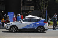 People wearing face masks look at a Baidu Apollo Robotaxi moving past a passenger pickup point setup at the Shougang Park in Beijing, Sunday, May 2, 2021. Chinese tech giant Baidu rolled out its paid driverless taxi service on Sunday, making it the first company that commercialized autonomous driving operations in China. (AP Photo/Andy Wong)