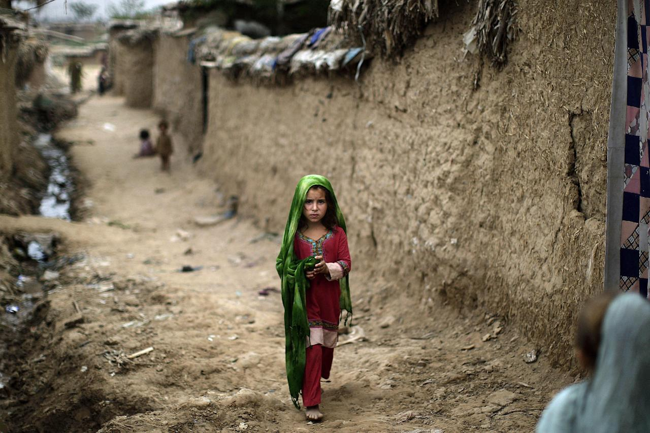 In this Tuesday, Aug. 14, 2012, photo, an Afghan refugee girl walks toward other girls in an alley of a slum on the outskirts of Islamabad, Pakistan. Hundreds of thousands of Afghan refugees are in limbo as Pakistan, increasingly frustrated with hosting the world's largest and longest-running refugee population, weighs whether to renew their refugee status by the end of this year. A large-scale return of the 1.7 million Afghan refugees currently living in Pakistan would be a massive problem for Afghanistan at a time when it's already struggling to maintain security in the face of an American troop withdrawal. But Pakistan increasingly seems to be angry at a refugee population that many feel has overstayed its welcome. (AP Photo/Muhammed Muheisen)