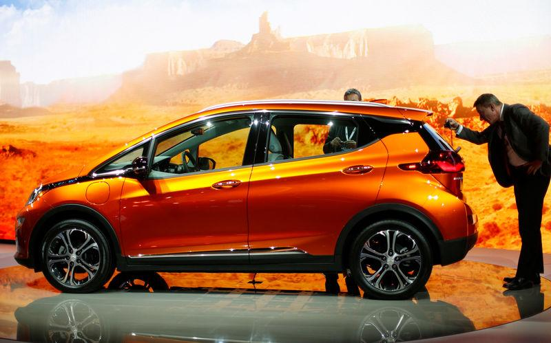 Show attendees look over a Chevrolet Bolt EV electric vehicle at the North American International Auto Show in Detroit