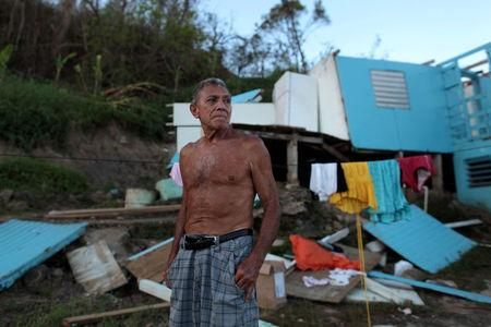 Ramon Sostre, stands in front of his damaged house after Hurricane Maria destroyed the town's bridge in San Lorenzo, Morovis, Puerto Rico, October 4, 2017. REUTERS/Alvin Baez