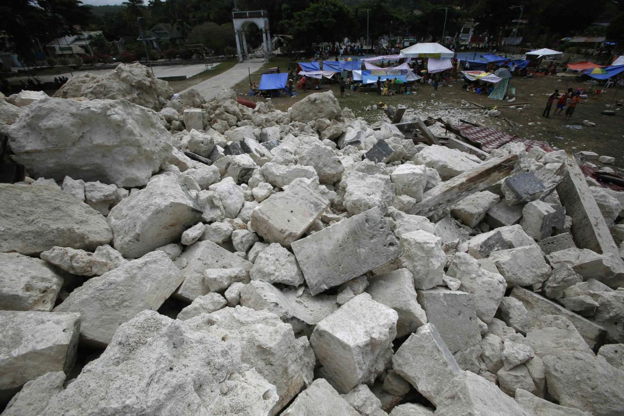 Residents stay in makeshift shelters in front of a heap of rubble from the collapsed centuries-old Our Lady of Light church in Loon, Bohol, a day after an earthquake hit central Philippines October 16, 2013. REUTERS/Erik De Castro (PHILIPPINES - Tags: DISASTER ENVIRONMENT)
