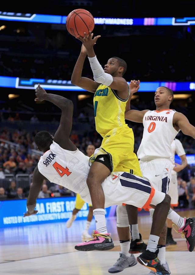 <p>Chris Flemmings #1 of the North Carolina-Wilmington Seahawks drives to the basket against Marial Shayok #4 of the Virginia Cavaliers during the first round of the 2017 NCAA Men's Basketball Tournament at Amway Center on March 16, 2017 in Orlando, Florida. (Photo by Mike Ehrmann/Getty Images) </p>