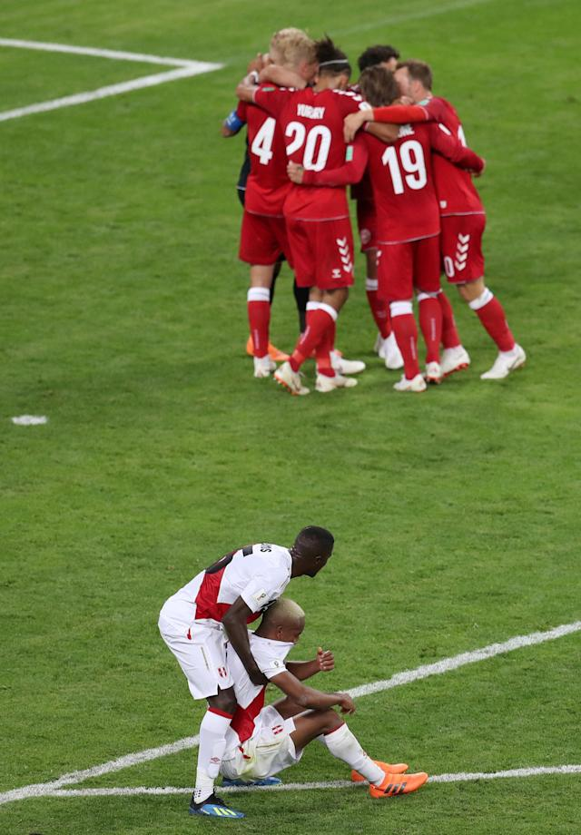 Soccer Football - World Cup - Group C - Peru vs Denmark - Mordovia Arena, Saransk, Russia - June 16, 2018 Peru's Christian Ramos helps Andre Carrillo as Denmark's players celebrate after the match REUTERS/Ricardo Moraes TPX IMAGES OF THE DAY