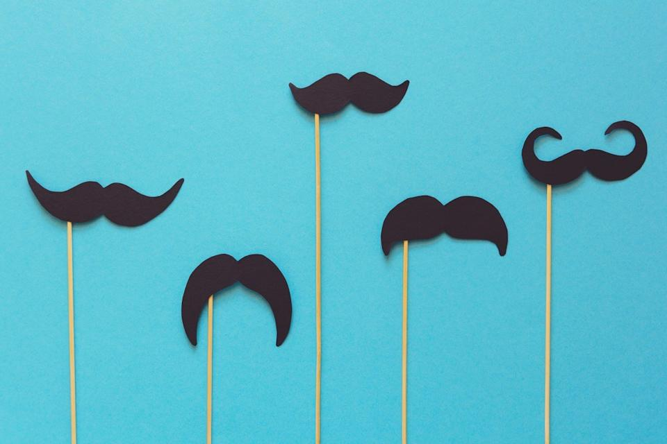 Paper moustache on booth props on blue paper background. Cut out style. Movember concept. Top view. Flat lay. Copy space. Toned (Paper moustache on booth props on blue paper background. Cut out style. Movember concept. Top view. Flat lay. Copy space.