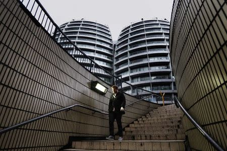 """A man walks down a flight of stairs near buildings surrounding the Old Street roundabout, dubbed """"Silicon Roundabout"""", in London, in this May 28, 2013 file photo. REUTERS/Luke Macgregor/Files"""