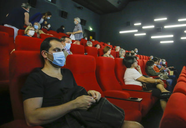 People wear protective masks as they wait for the screening of a movie in Paris, Monday, June 22, 2020. Movie theaters are reopening across the country after three months of closure due to the COVID-19 lockdown measures. (AP Photo/Michel Euler)