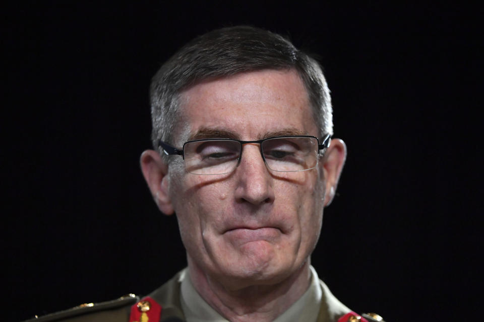 Chief of the Australian Defence Force Gen. Angus Campbell bites his lips while delivering the findings from the Inspector-General of the Australian Defence Force Afghanistan Inquiry, in Canberra, Thursday, Nov. 19, 2020. A shocking report into war crimes by elite Australian troops has found evidence that 25 soldiers unlawfully killed 39 Afghan prisoners, farmers and civilians. (Mick Tsikas/Pool Photo via AP)