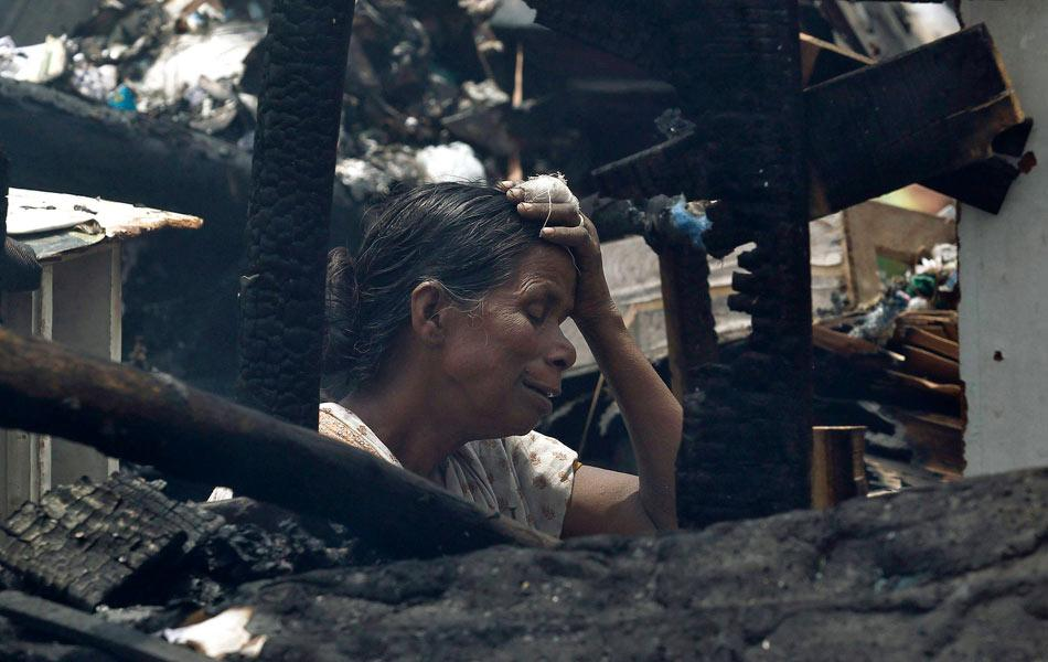 A local resident weeps amid her burnt belongings after a fire broke out in a slum area in New Delhi June 22, 2012. Hundreds of huts were gutted in the fire but no casualties were reported and the cause of the fire was unknown, local media reported on Friday. REUTERS/Adnan Abidi