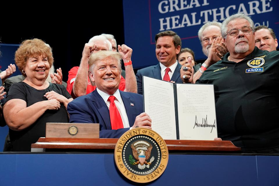 U.S. President Donald Trump holds up an executive order on Medicare he signed during an event at The Villages retirement community in The Villages, Florida, U.S., October 3, 2019. REUTERS/Kevin Lamarque
